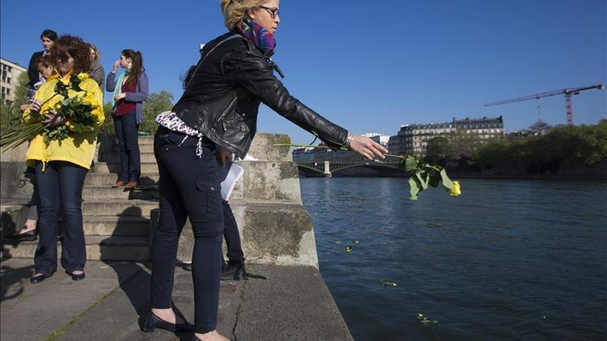 Una mujer lanza una rosa al río Sena durante una marcha organizada por Amnistía Internacional para rendir homenaje a las víctimas de los últimos naufragios en el Mediterráneo. / Efe.