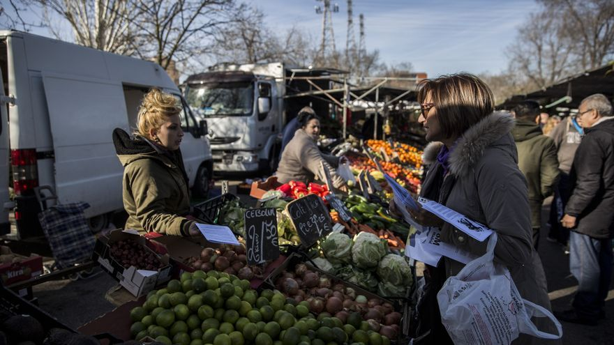 Dos mujeres en un mercado de Madrid comparten información sobre la huelga del próximo 8 de marzo.