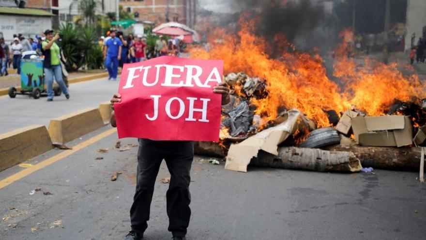 Manifestantes y policías se enfrentan en una protesta para pedir la salida Hernández