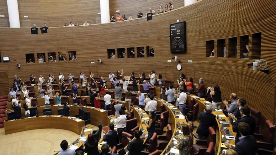 Los diputados de las Corts Valencianes aplauden a los representantes de las víctimas del metro tras la aprobación del dictamen parlamentario sobre el accidente.