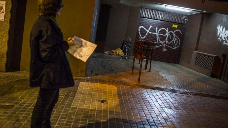 Una voluntaria contabilitza una persona sense sostre dormint a la entrada d'un garatge / ENRIC CATALÀ