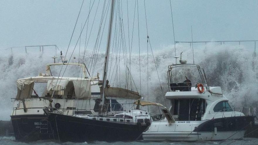 Grandes olas sobrepasan el espigón del Puerto Olímpico de Barcelona ayer.