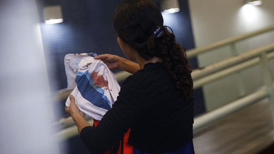 La madre del niño fallecido sostiene su camiseta ensangrentada