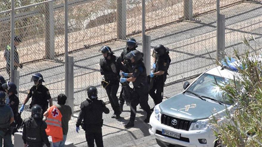 Miembros de la Guardia Civil trasladan a un inmigrante en la valla fronteriza de Ceuta. Archivo