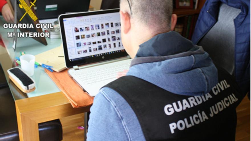 Agente de la Policía Judicial de la Guardia Civil con un ordenador con pornografía infantil