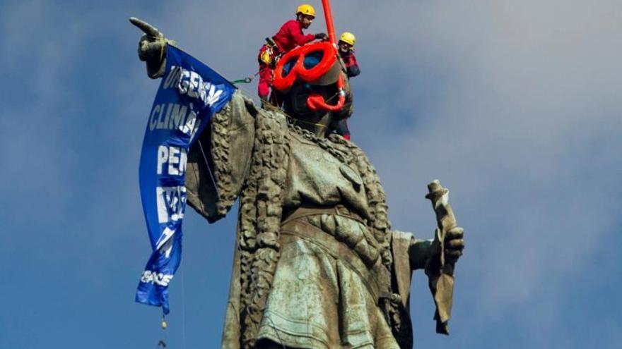 Dos activistas de Greenpeace colocan unas gafas de buzo a la estatua de Colón