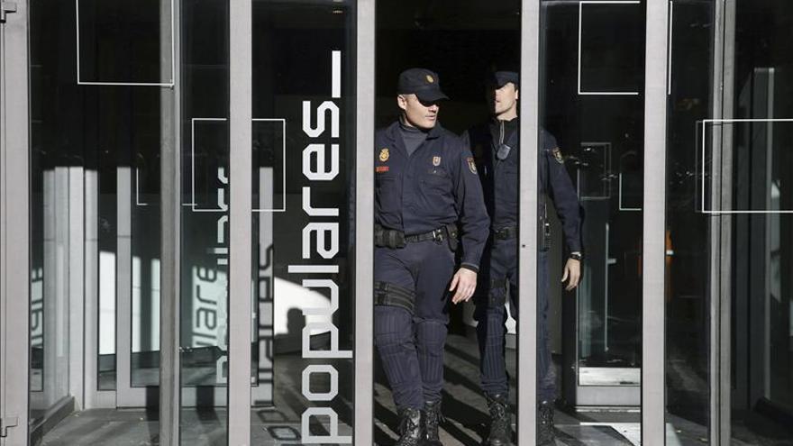 Dos agentes de la Policía Nacional durante el registro de la sede nacional del PP
