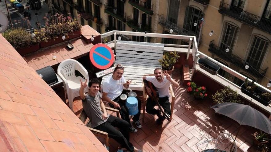 Fotografía cedida por Stay Homas de los componentes del grupo barcelonés  (Klaus Stroink, Guillem Boltó y Rai Benet) retratados por un vecino en su terraza del Eixample, desde donde graban las #confinationsongs.