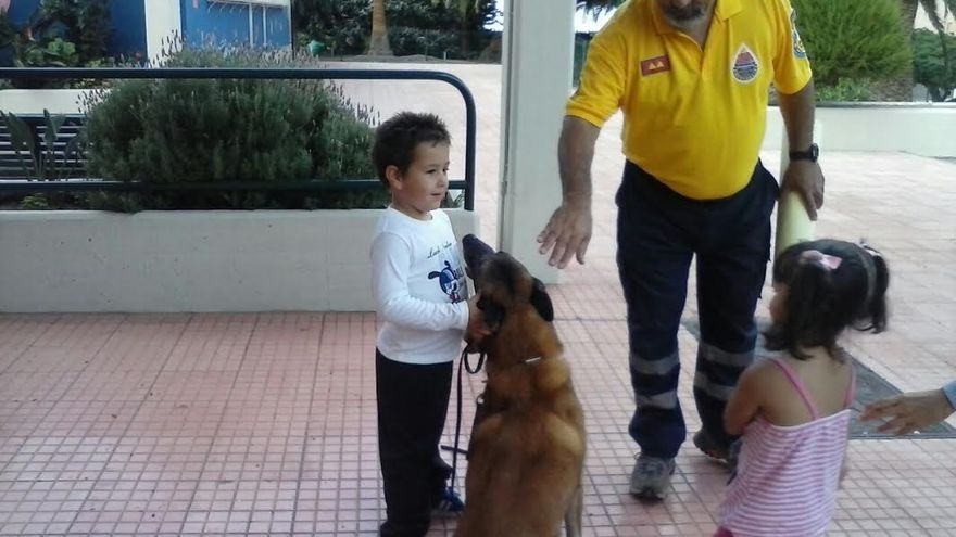 En la imagen, Francisco Hernández, coordinador del Grupo de Rescate Canino de AEA, con dos escolares y uno de los perros de salvamento.