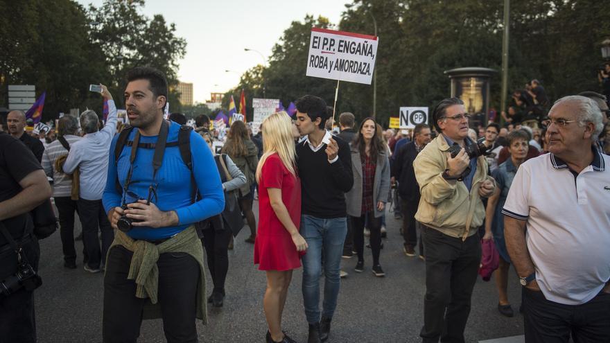 """Dos manifestantes se besan bajo una pancarta crítica con el Partido Popular: """"El PP engaña, roba y amordaza"""""""