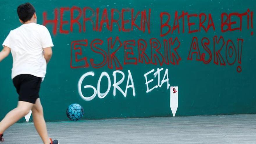 Un niño juega en un frontón con pintadas de ETA.
