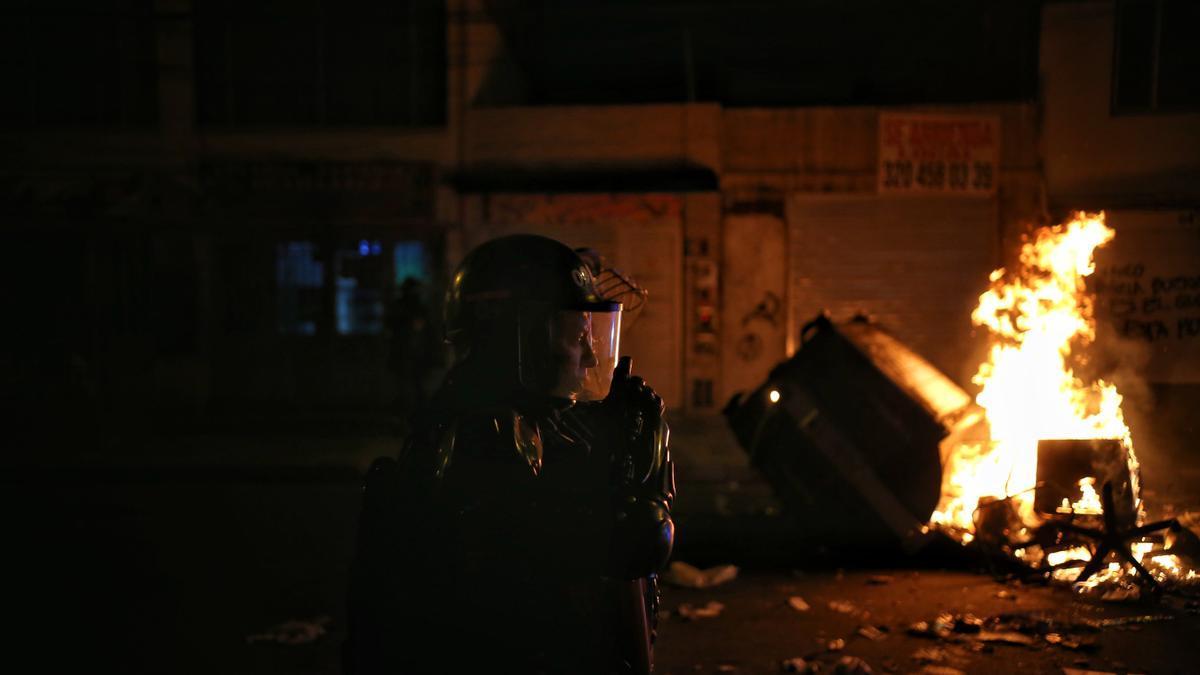 9 de septiembre de 2020. Un policía junto a un cubo de basura en llamas durante los enfrentamientos con los manifestantes en medio de protestas por la muerte de un hombre después de una operación policial.