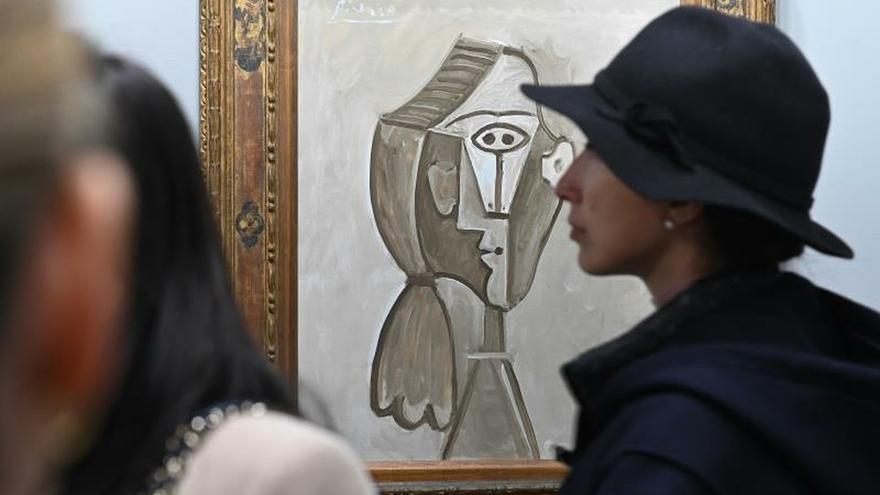 """Varios visitantes conversan delante de la obra """" Retrato de Jaqueline"""", de Pablo Ruiz Picasso, expuesta en el espacio dedicado a la galería Edward Tyler Nahem, durante la primera jornada de la Feria Internacional de Arte Contemporáneo de Madrid (ARCO), este miércoles, en Madrid."""