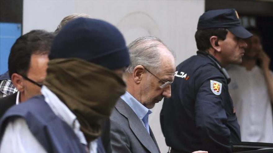 Rodrigo Rato sale de su vivienda en Madrid escoltado por agentes de Aduanas.