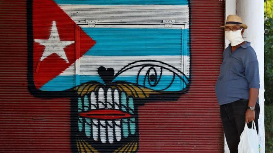 Un hombre con mascarilla espera en una calle de La Habana.