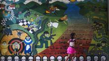 Una niña camina junto a uno de los murales que recuerdan el conflicto armado interno de El Salvador en Carasque
