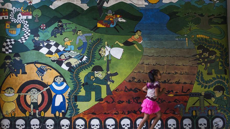 Una niña camina junto a uno de los murales que recuerdan la guerra en Nueva Trinidad