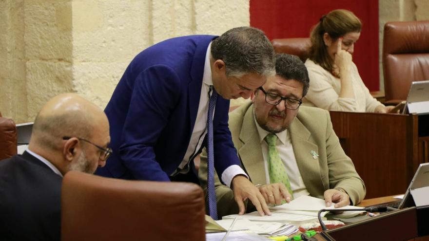 El consejero de Presidencia, Elías Bendodo, se acerca a la bancada de Vox para negociar con Francisco Serrano durante el debate.