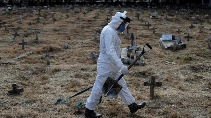 Un sepulturero camina por las tumbas después de finalizar el entierro de Nazareno Rodrigues Costa, de 72 años, que murió con sospecha de Covid-19, este miércoles, en el cementerio de Cajú, en Río de Janeiro (Brasil).