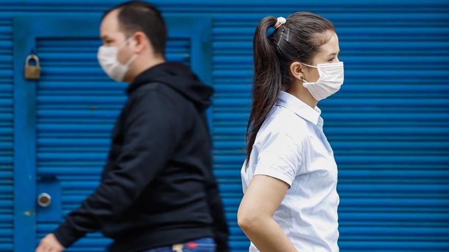 Transeúntes caminan con tapabocas el 13 de abril de 2020 en Asunción (Paraguay).