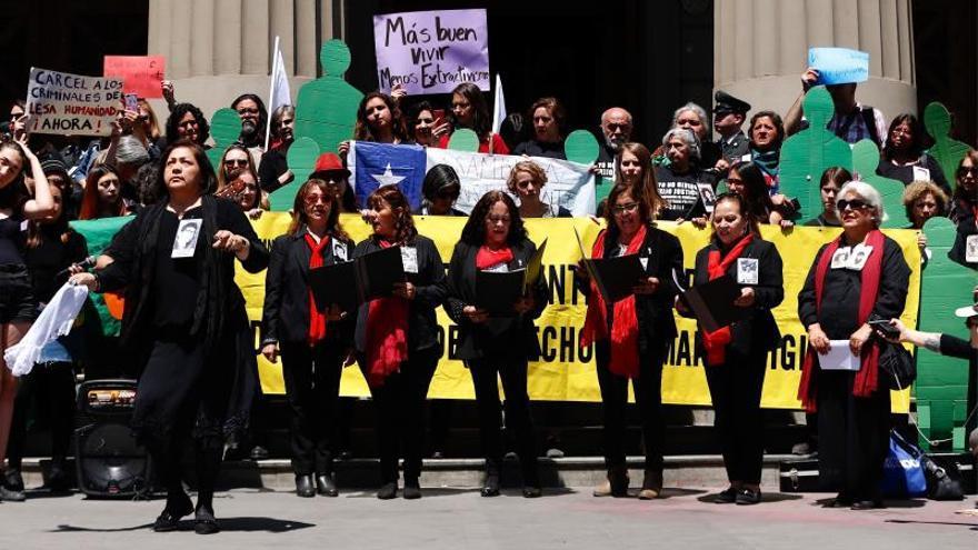 Manifestantes en una protesta para exigir sanciones contra los presuntos responsables de las muertes y torturas por parte de agentes del Estado, frente al Palacio de Tribunales en Santiago (Chile).