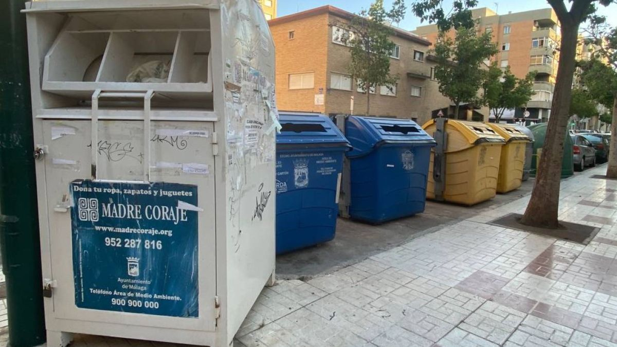 En primer término, contenedor habilitado para la donación de ropa en Málaga.