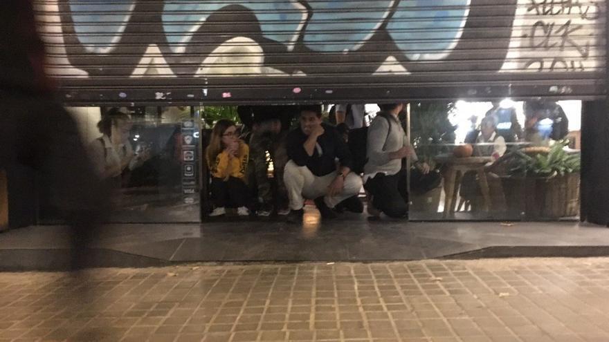 Gente escondida en los comercios en la cuarta jornada de protestas en Barcelona.