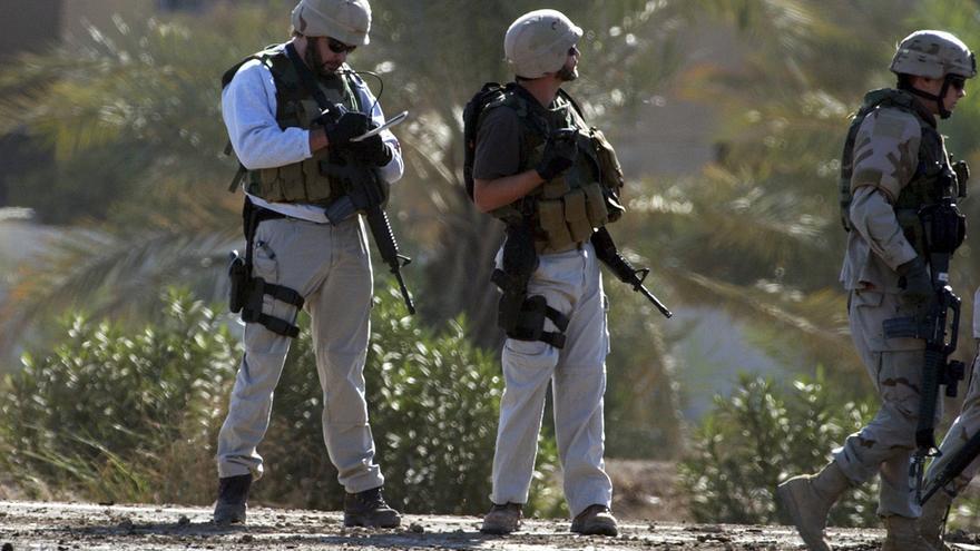 Dos trabajadores militares privados investigan el lugar en el que estalló una bomba cerca de Bagdad (Irak), en noviembre de 2004