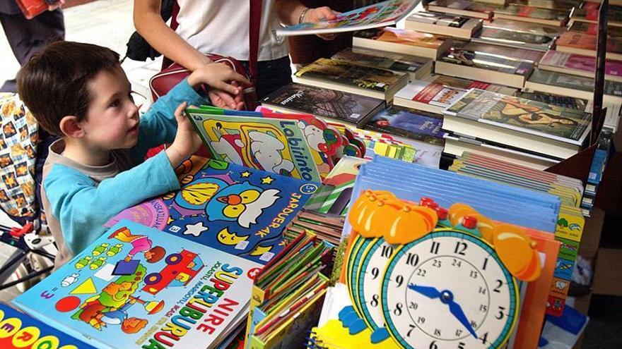 Un niño examina publicaciones en euskera destinadas a su edad en un puesto de libros.