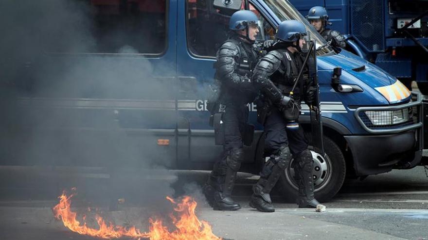 Agentes antidisturbios se protegen durante un enfrentamiento con manifestantes contra la reforma laboral en París.