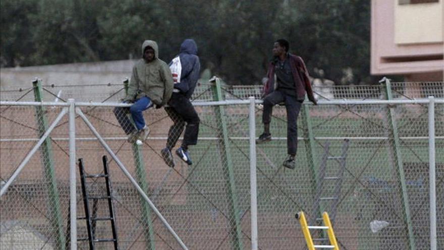 Tres inmigrantes subsaharianos permanecen encaramados en lo alto de la valla de Melilla cuatro horas después de registrarse un intento de entrada masiva en la zona cercana al paso fronterizo de Barrio Chino/ Efe