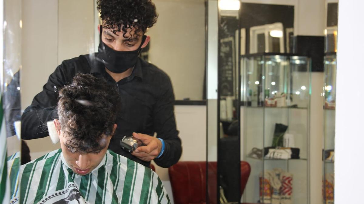 Otman corta el pelo a uno de sus clientes