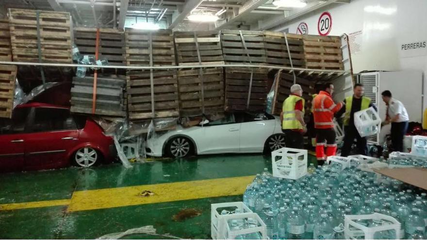 Vuelca una plancha cargada de garrafas de aguas sobre varios vehículos.