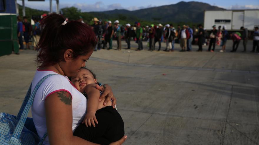 Una mujer lleva a su bebé en una fila de migrantes en un puñado de autobuses que ayudan a transportar a familias con niños pequeños hasta la próxima parada, en Niltepec, México, el martes 30 de octubre de 2018. La caravana de migrantes que avanza lentamente por el sur de México exige que el gobierno mexicano ayude a sus 4.000 miembros a llegar a la Ciudad de México.