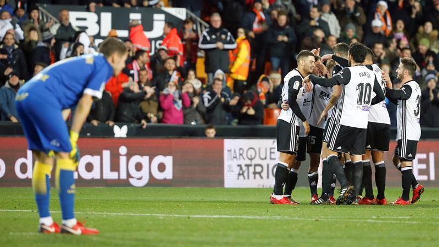 Los jugadores del Valencia CF celebran el cuarto gol del equipo valencianista durante el partido de octavos de final de la Copa del Rey y Raul Lizoain se lamenta. EFE/Kai Försterling