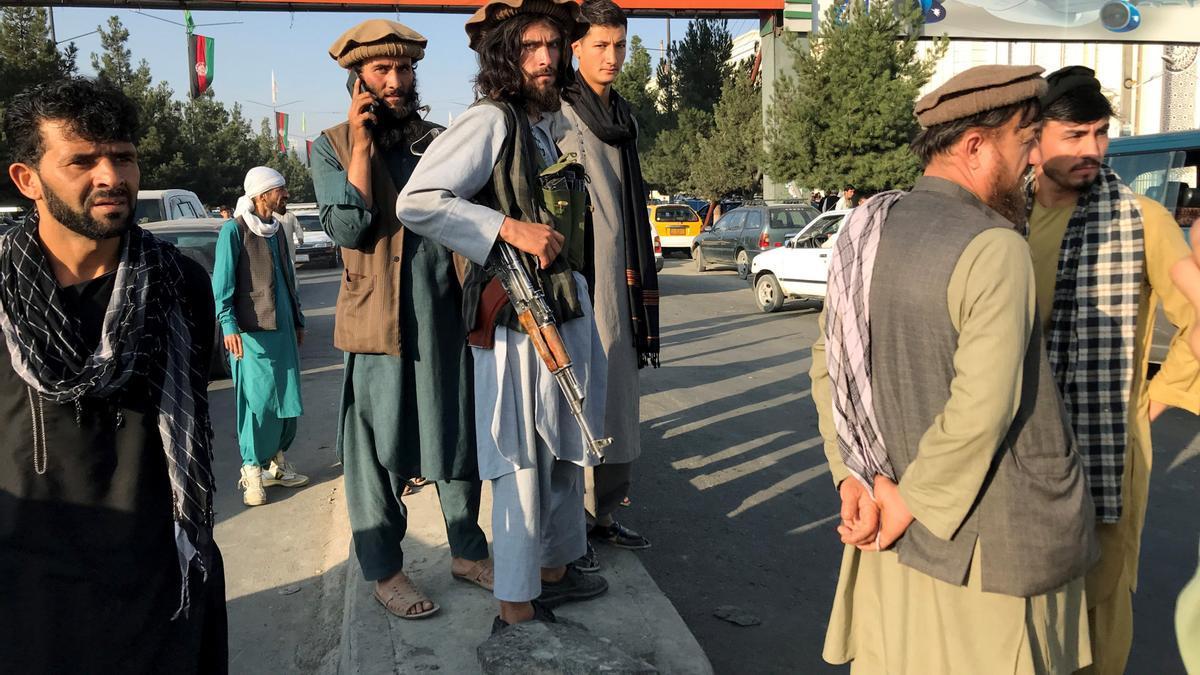 Un miliciano talibán rodeado de hombres a las puertas del aeropuerto de Kabul.