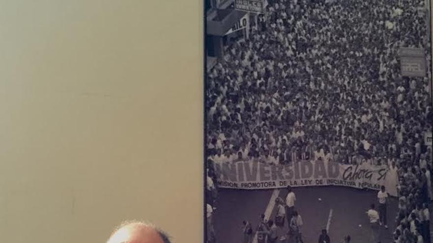 Ángel Tristán Pimienta posa ante una fotografía de la manifestación pro-universidad de Las Palmas de Gran Canaria.
