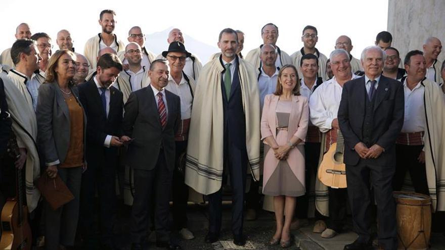 Felipe VI posa con la ministra de Fomento, Ana Pastor (3d), y el presidente en funciones de Canarias, Paulino Rivero (3i), entre otros, junto al grupo musical canario Los Sabandeños. (EFE/Cristóbal García).