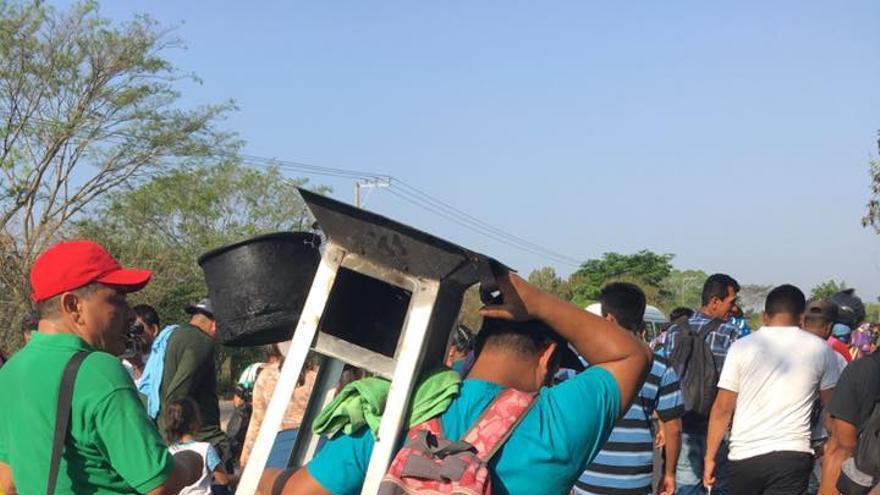 Uno de los migrantes del 'viacrucis' porta una estufa durante el recorrido.