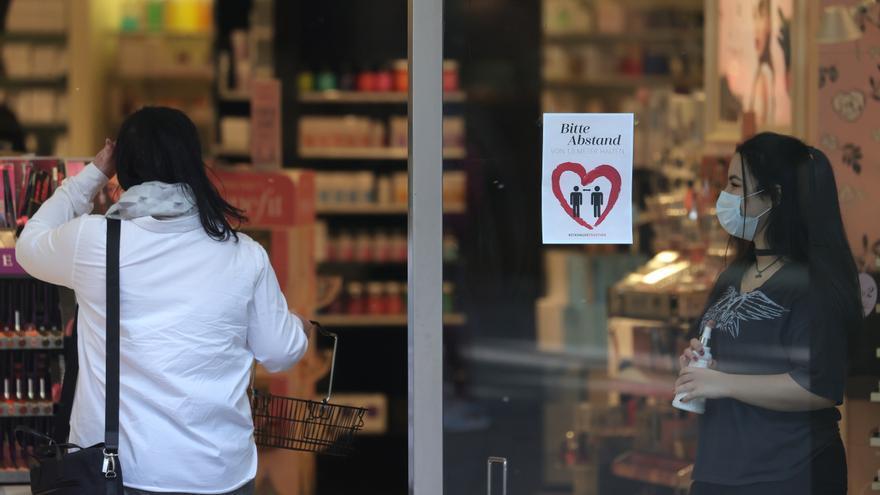 Una vendedora con mascarilla se encuentra en la entrada de una perfumería en Essen, Alemania, el 20 de abril de 2020.