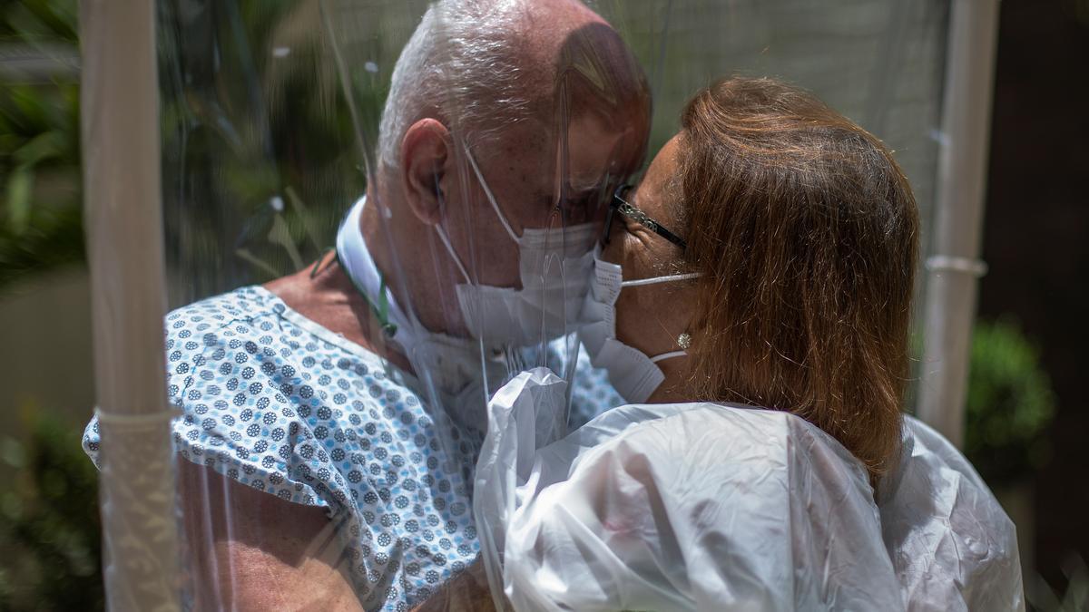Una pareja se besa a través de un plástico