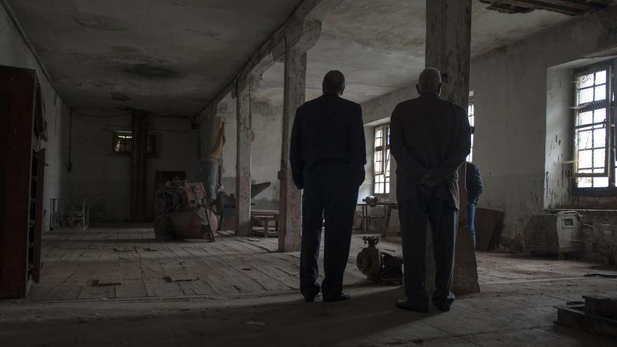 Dos familiares de los fallecidos en la cárcel contemplan una de sus galerías, en la planta baja. Por debajo transcurre el río Ebro, donde se encontraban las celdas de castigo y a veces los allí enviados soportaban el agua a la altura del cuello | Álvaro Minguito \ DISO Press