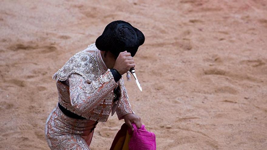 Un torero alza el puñal (puntilla) para rematar al toro, previamente torturado en la plaza y ya en el suelo, herido por la espada. Pamplona, Sanfermines 2014. Foto: Tras los Muros