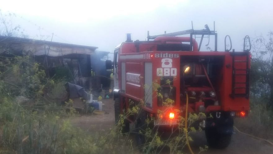 En la imagen, pajero afectado por el incendio y un camión de Bomberos La Palma.