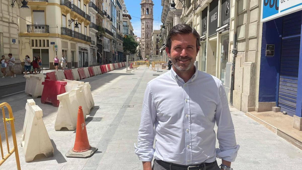 Rafael Torres, frente a su comercio en la calle de la Paz de València, tomada por las obras de peatonalización de la plaza de la Reina.