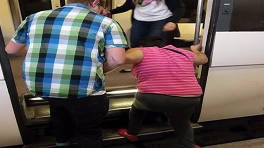 Una persona con movilidad reducida accede a un tren de Cercanías con la ayuda de otra persona