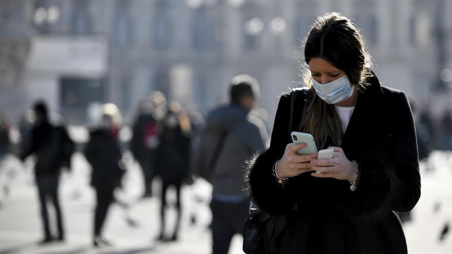 Una mujer con máscara usa el móvil en Milán, Italia // Claudio Furlan/Lapresse via AP