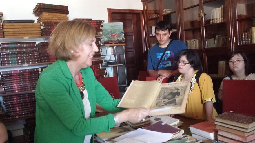 En la imagen, Ángeles Morales muestra a los integrantes de Padisbalta un documento antiguo.