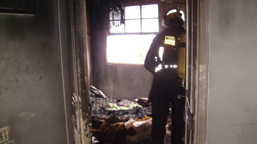 En la imagen, un bombero en la habitación de la vivienda donde ardió el colchón. Foto: BOMBEROS LA PALMA.
