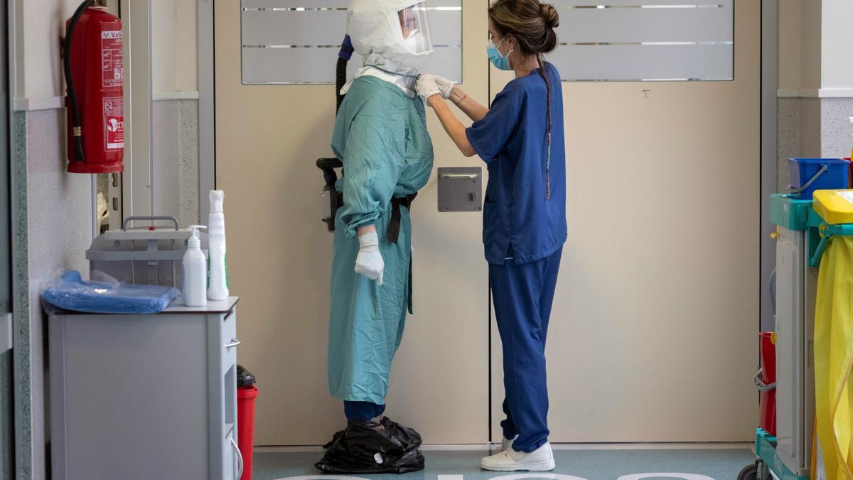 Una enfermera ajusta el Equipo de Protección Personal (EPI) a un enfermero antes de entrar a un box de la Unidad de Cuidados Intensivos (UCI).